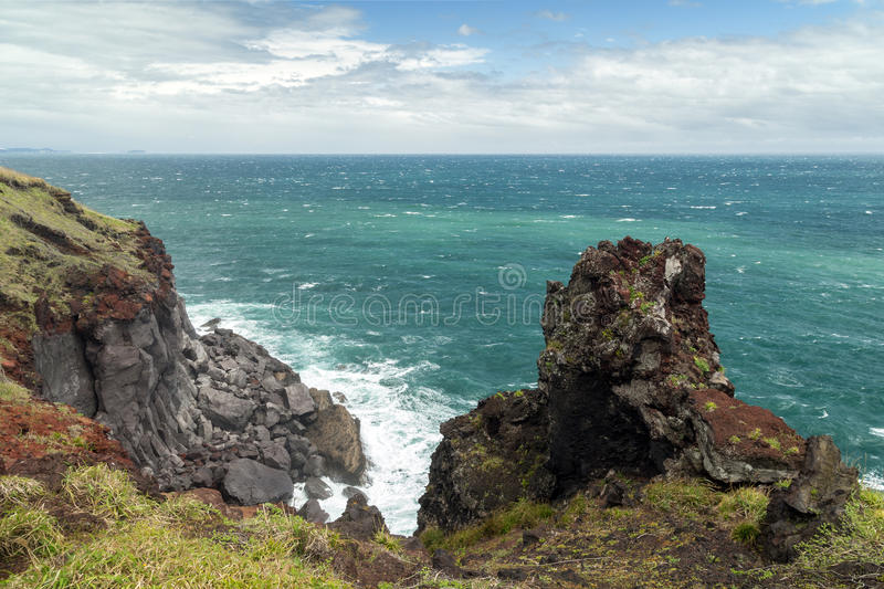 Rugged crag, steep cliff and ocean on Jeju Island. View of an ocean, rugged crag and steep cliff next to the Songaksan Mountain on Jeju Island in South Korea stock images