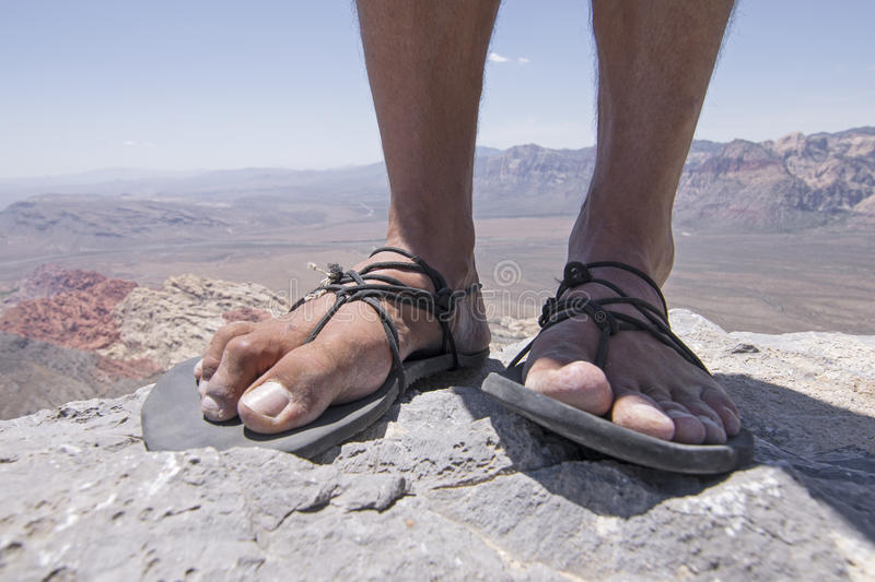 Rugged feet in primitive sandals on mountain. Closeup of weathered worn male feet and toes in primitive simple sandals with black laces standing on top of rocky stock photography