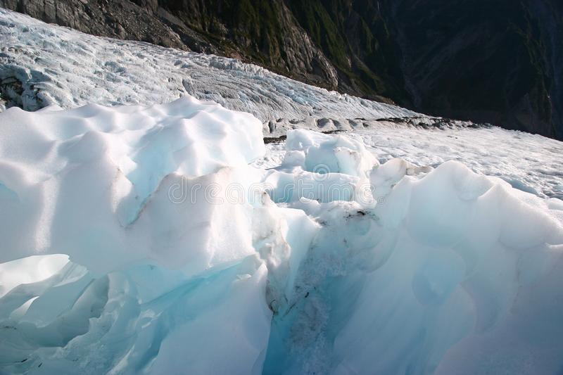 Rugged blue glacier ice chunks on mountain stock images