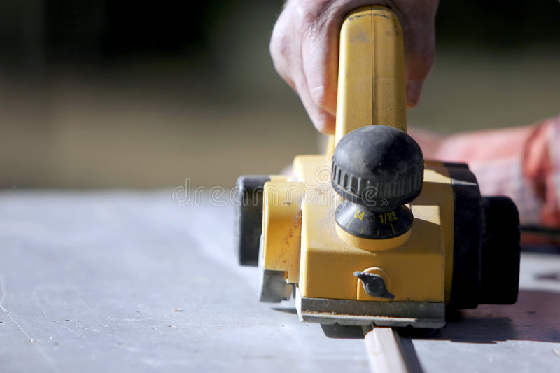 Rugged Hand & Power Tool. Close-up of a construction worker's hand and power tool while planing a piece of wood trim for a project (shallow focus stock photo
