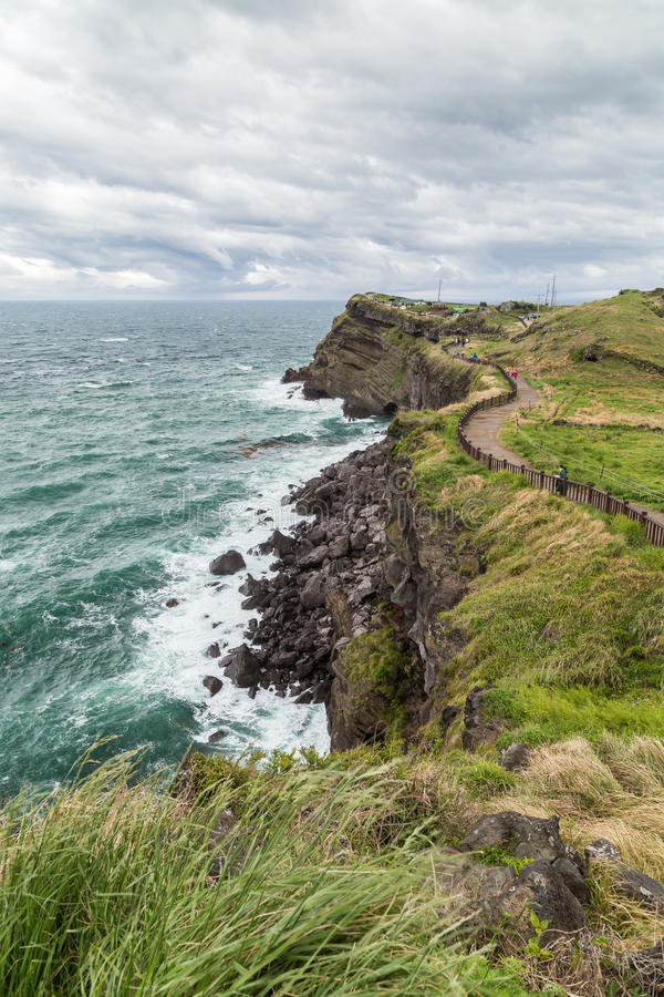 Rugged landscape and coastal walkway on Jeju Island. View of rugged landscape and coastal walkway next to the Songaksan Mountain on Jeju Island in South Korea stock photo