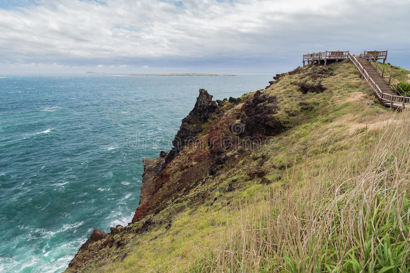 Rugged landscape and coastal walkway on Jeju Island. View of rugged landscape and coastal walkway next to the Songaksan Mountain on Jeju Island in South Korea royalty free stock images