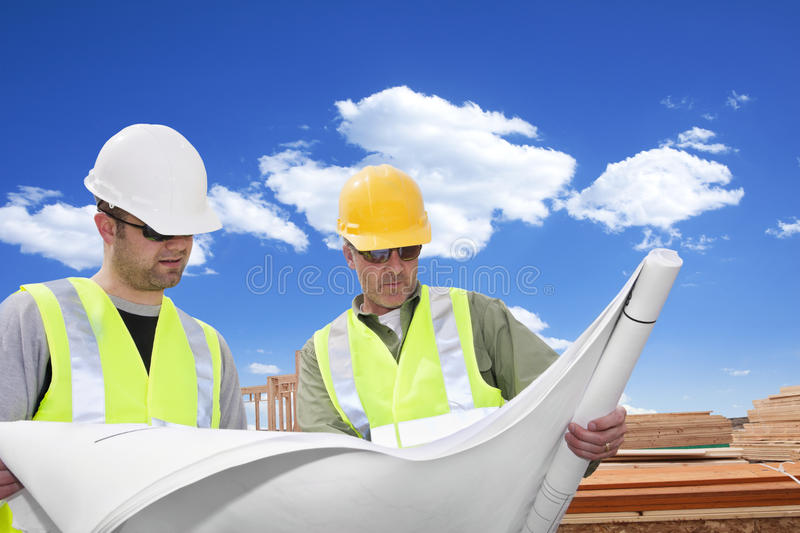 Rugged Male Architects looking at a blueprint. Rugged, tough male mature architects looking at the blueprints of a construction project stock photography