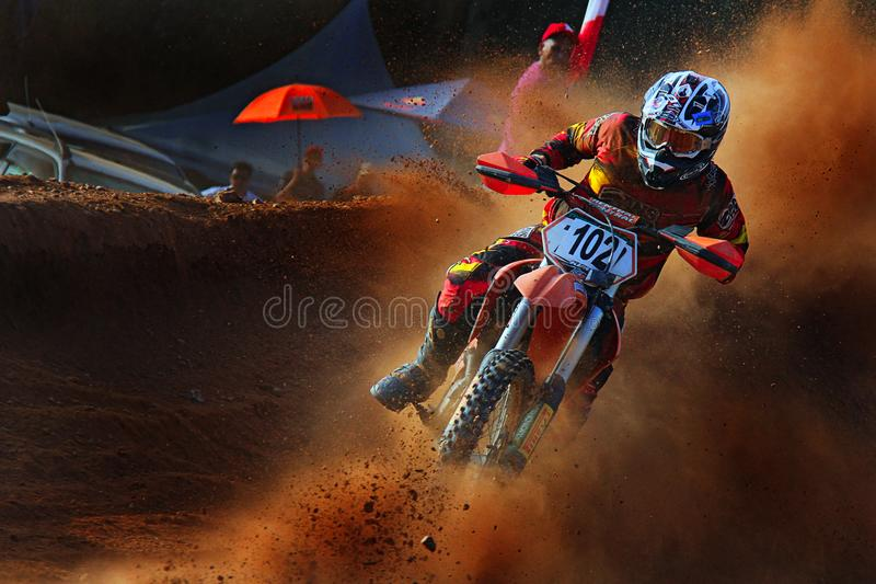 a rugged motorcycle rider is taking a sharp turn in the motocross tournament royalty free stock photography