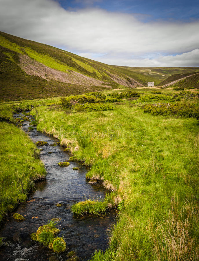 Rugged mountain landscape at Lecht Mine Scotland. Rugged mountain landscape with stream at Lecht Mine in Scotland at summertime royalty free stock images