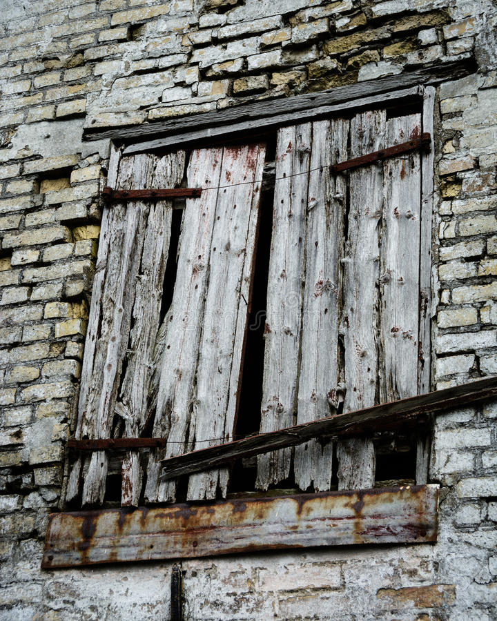 Rugged and rusty. An old barn opening with tree blinds in a brick wall - decay, vintage, rugged and rusty stock photography