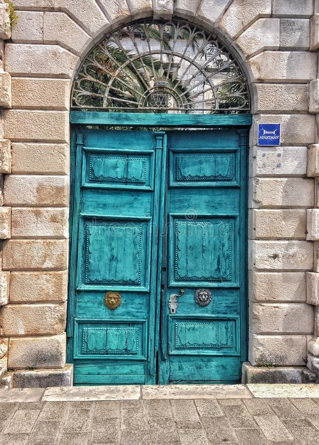 Rugged turquoise doors. Old double turquoise rugged tree doors with lion knobs from Dubrovnik stock photos