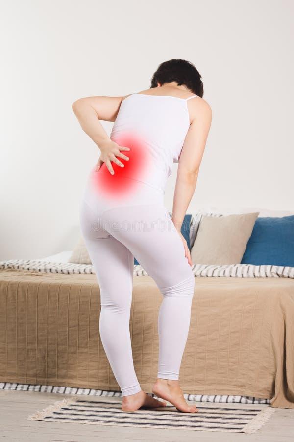 Rugpijn, nierontsteking die, vrouw aan rugpijn thuis lijden stock foto