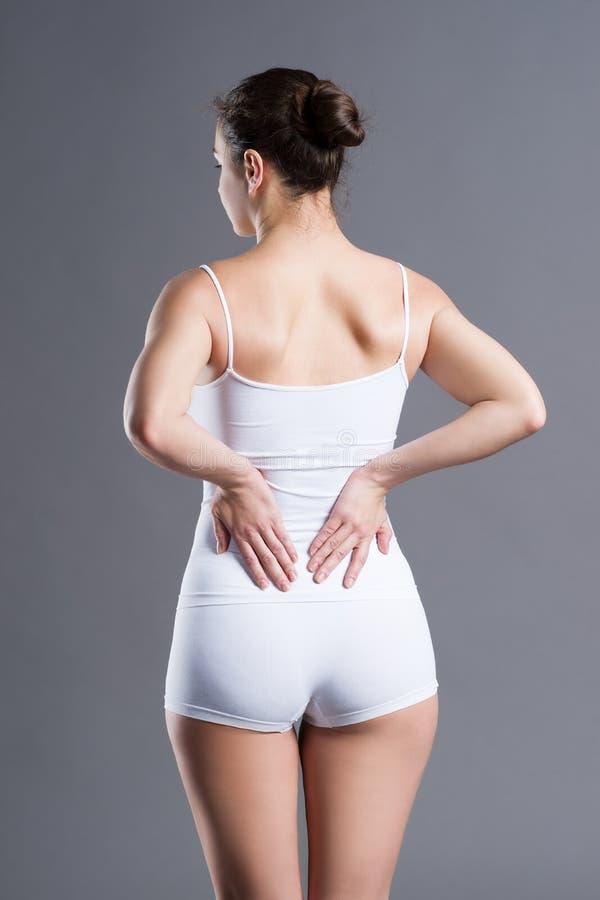 Rugpijn, nierontsteking, pijn in vrouwen` s lichaam stock afbeeldingen