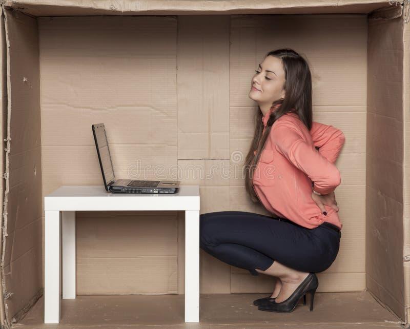 Rugpijn van een slechte positie in het bureau royalty-vrije stock afbeelding