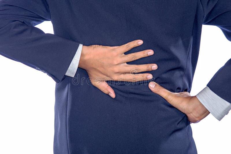 Rugpijnconcept die over in pijn die met handen buigen lagere B houden stock foto