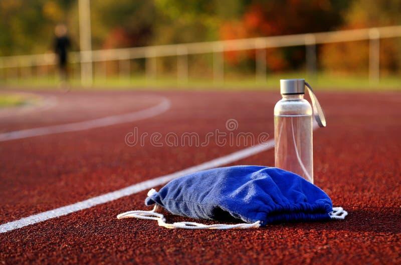 Rugzak en waterfles op atletisch spoor royalty-vrije stock foto's