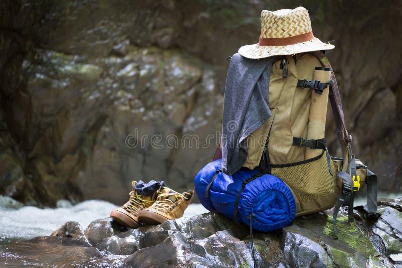Rugzak met de rust van het reismateriaal op een rots royalty-vrije stock foto's