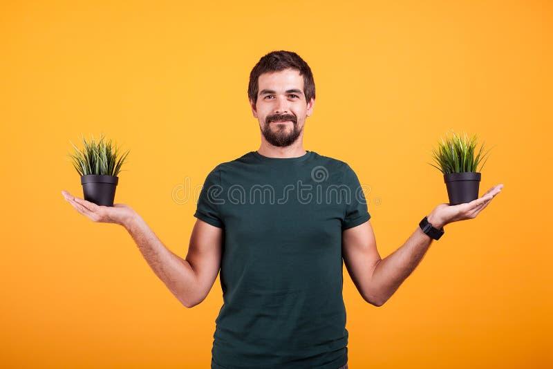 Ruhekonzeptbild des entspannten Mannes zwei Töpfe Gras halten lizenzfreie stockfotografie