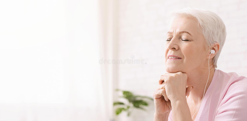 Ruhige ältere Frau, die, hörend klassische Musik meditiert stockbilder