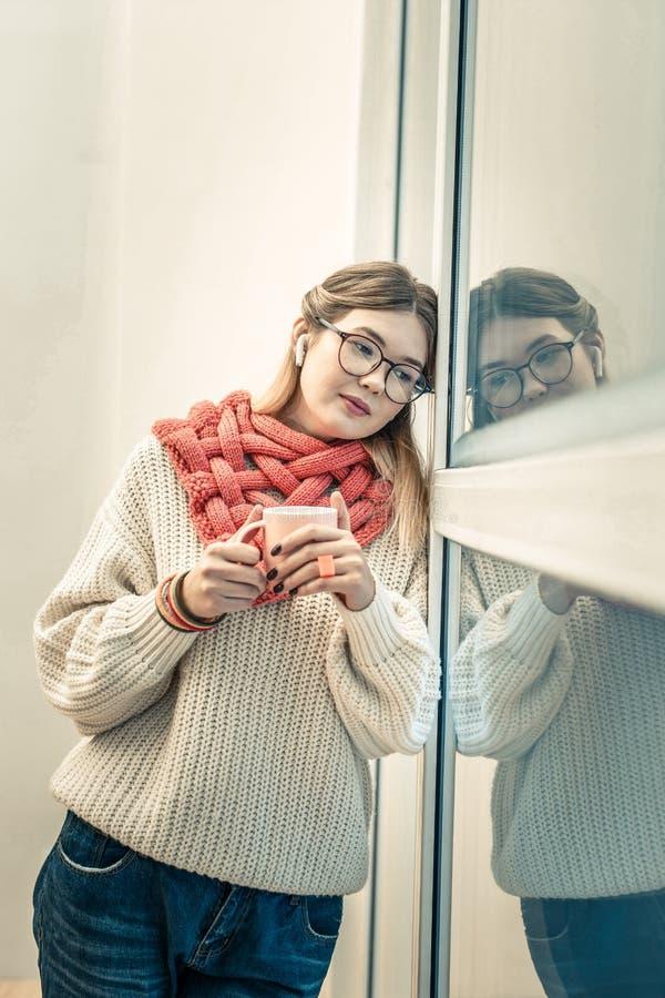 Ruhige anziehende Frau in der gestrickten Strickjacke, die auf Plastikfenster sich lehnt stockbild