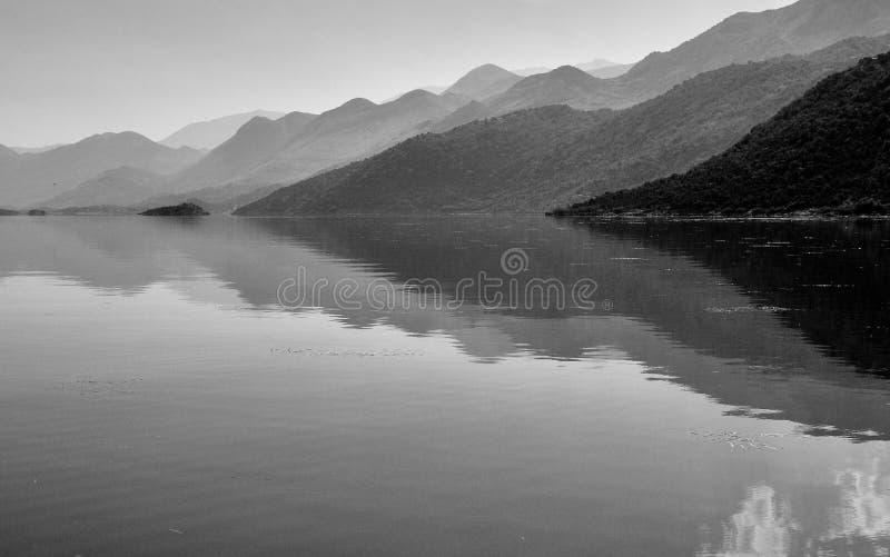 Ruhige Atmosphäre auf dem See Skadar in Montenegro mit Bergen hinten stockbild