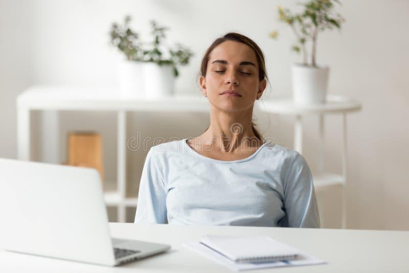 Ruhige attraktive Frau, die am Arbeitsplatz mit geschlossenen Augen sich entspannt lizenzfreie stockbilder