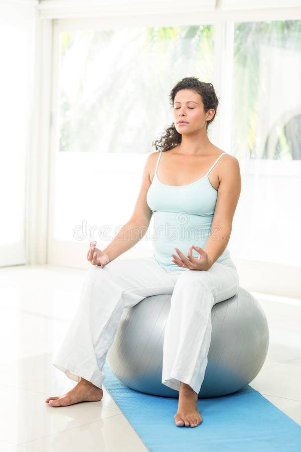 Ruhige blonde schwangere Frau, die auf Übungsball sitzt lizenzfreies stockfoto