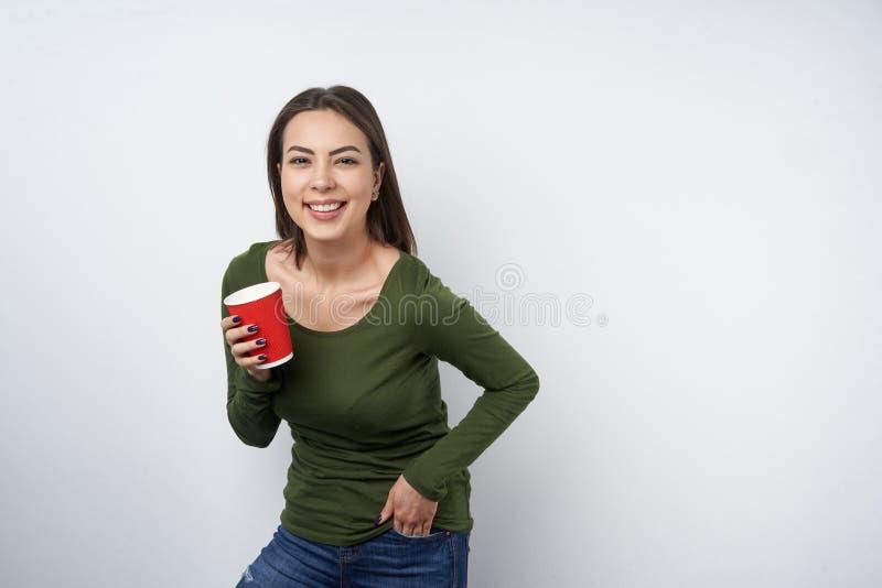 Ruhige brunette Frau, die Wegwerfpapierbecher hält lizenzfreie stockfotografie