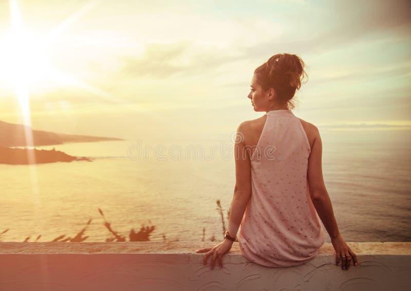 Ruhige Dame des Brunette, die einen schönen Sonnenuntergang aufpasst stockfotografie