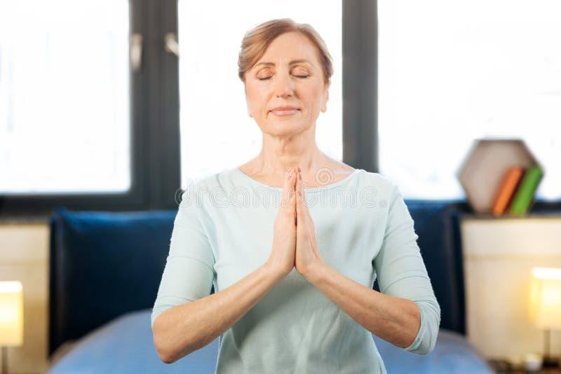 Ruhige erwachsene Frau, die im nachdenklichen Zustand beim Haben von Yogasitzung ist lizenzfreie stockfotografie