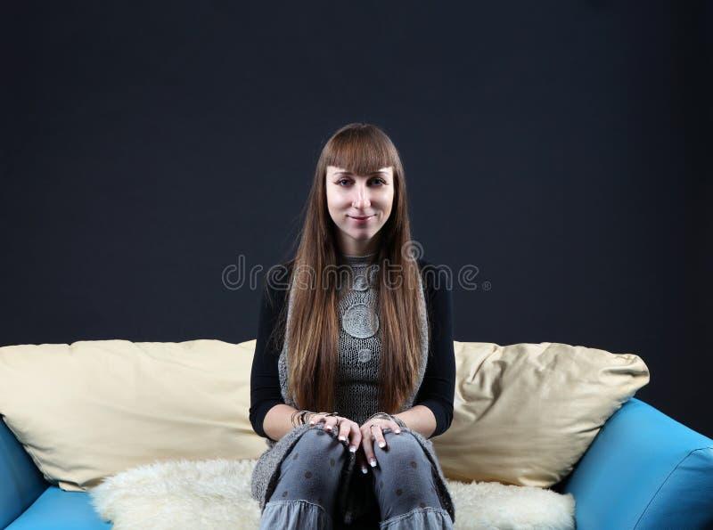 Ruhige Frau mit dem langen Haar, das auf der Couch sitzt lizenzfreie stockfotografie