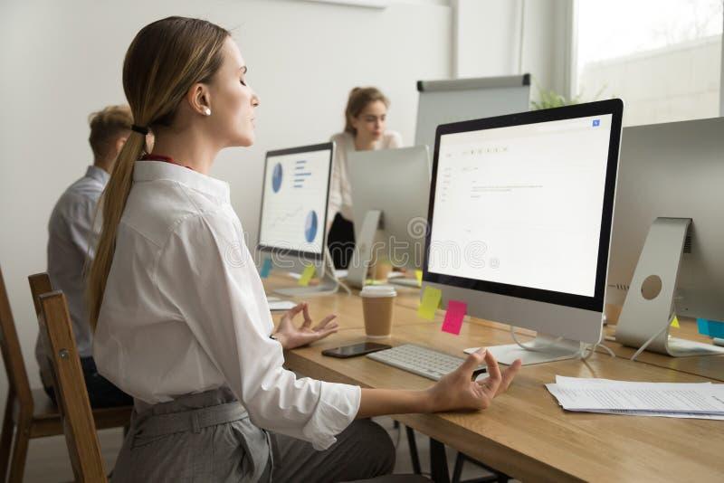 Ruhige ruhige Geschäftsfrau, die am Büroarbeitsschreibtisch, Seite meditiert stockbild