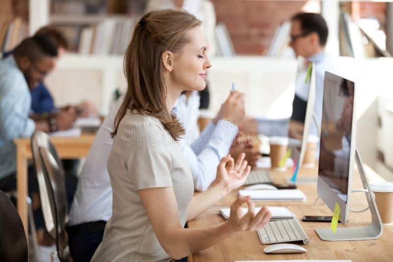 Ruhige Geschäftsfrau, die Yogaübung am Arbeitsplatz tut stockfotografie