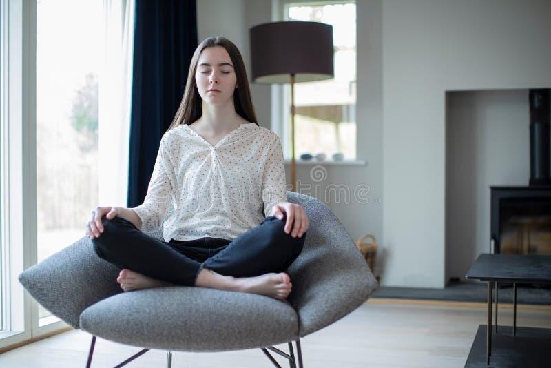 Ruhige Jugendliche-meditierendes im Stuhl zu Hause sitzen lizenzfreie stockfotografie