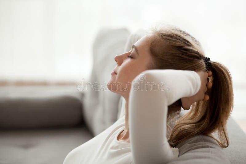 Ruhige junge Frau auf Couch zu Hause sich entspannen lizenzfreie stockfotos