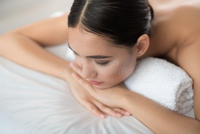 Ruhige junge Frau, die am Badekurort stillsteht stockfotografie