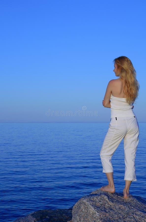 Ruhige junge Frau, die das Meer betrachtet lizenzfreies stockfoto