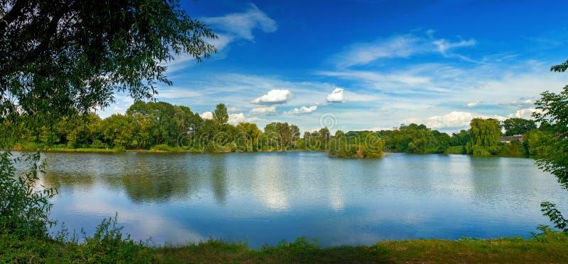 Ruhige Landschaft an einem See, wenn Weißwolkenhimmel und die Bäume im sauberen blauen Wasser reflektiert sind stockfoto