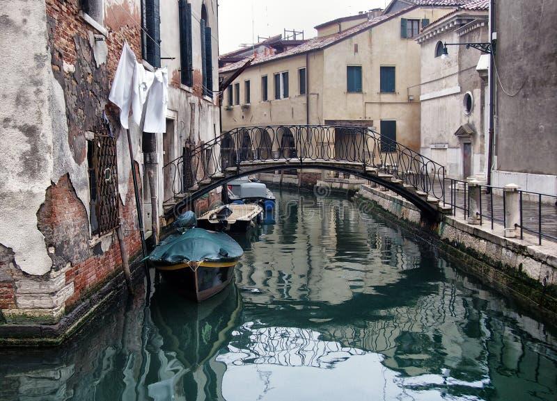 Ruhige leere Straße in Venedig auf einem Wintermorgen mit einer Brücke, die den Kanal und die alten Gebäude reflektiert im Wasser stockfoto