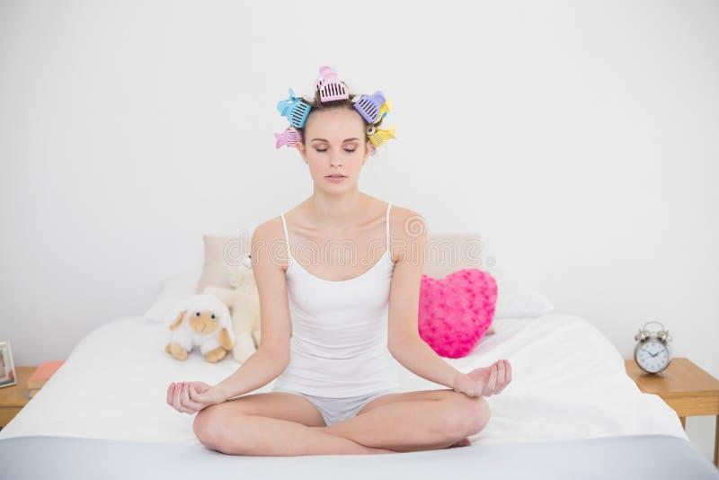 Ruhige natürliche braune behaarte Frau in den Haarlockenwicklern, die Yoga üben stockbild