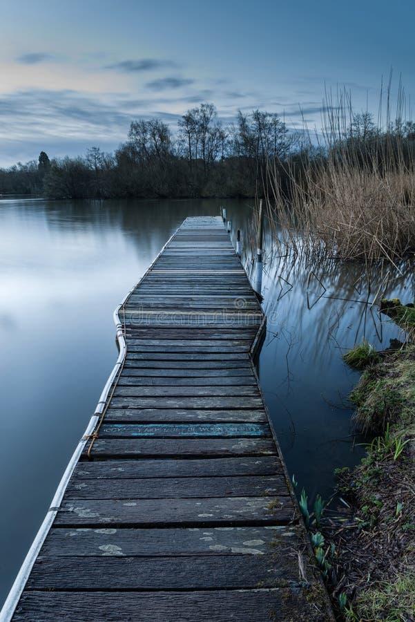 Ruhige ruhige mondbeschiene Landschaft über See und Anlegestelle stockfotografie