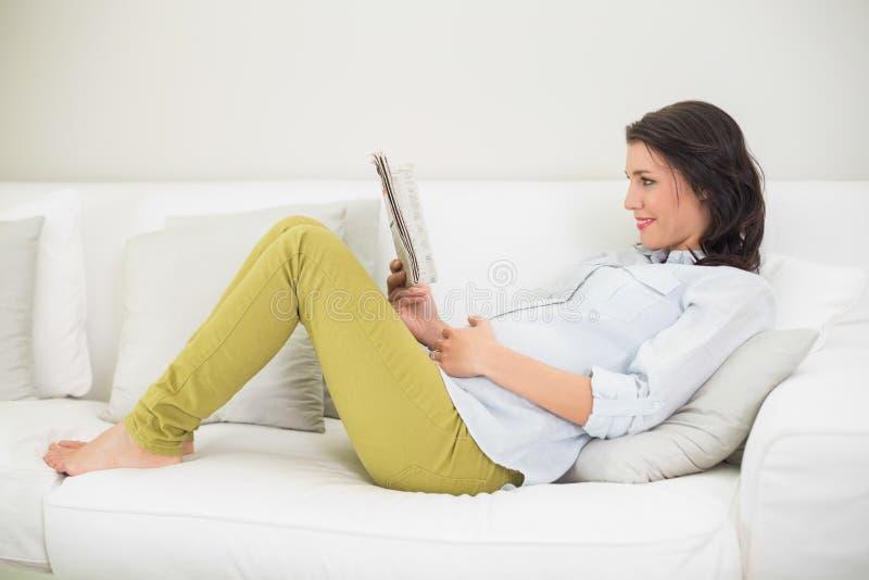 Ruhige schwangere braune behaarte Frau, die eine Zeitung liest lizenzfreie stockbilder