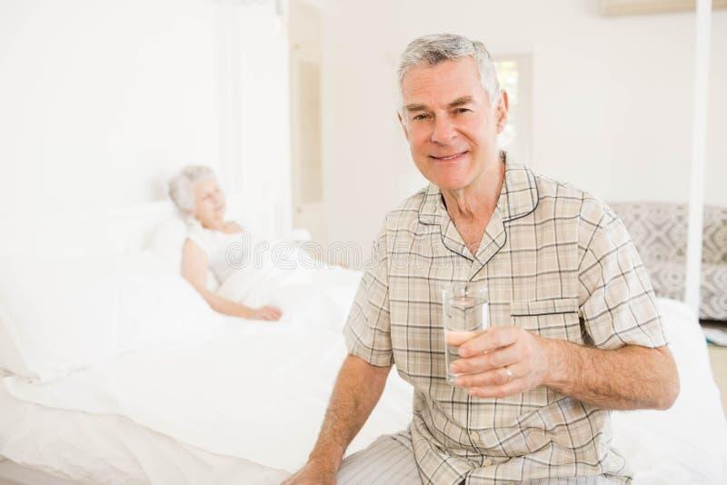 Ruhiger älterer Mann, der Glas Wasser hält lizenzfreie stockfotos