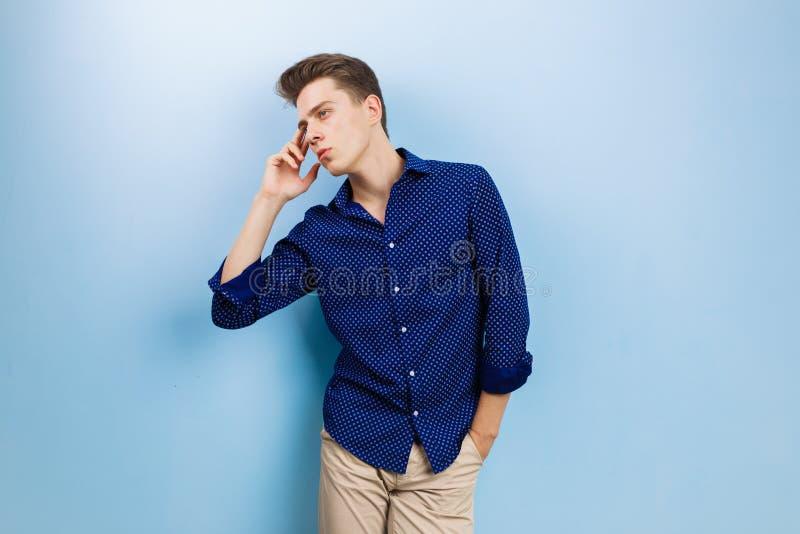 Ruhiger durchdachter hübscher dunkelhaariger Kerl, der blaues Hemd und beige die Hosen, stehend gegen blaue Wand trägt stockfotografie