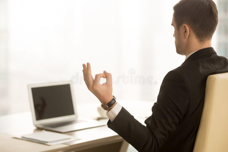Ruhiger Geschäftsmann, der an Arbeitsplatz, Kinn mudra, Yoga an wo meditiert lizenzfreie stockfotos