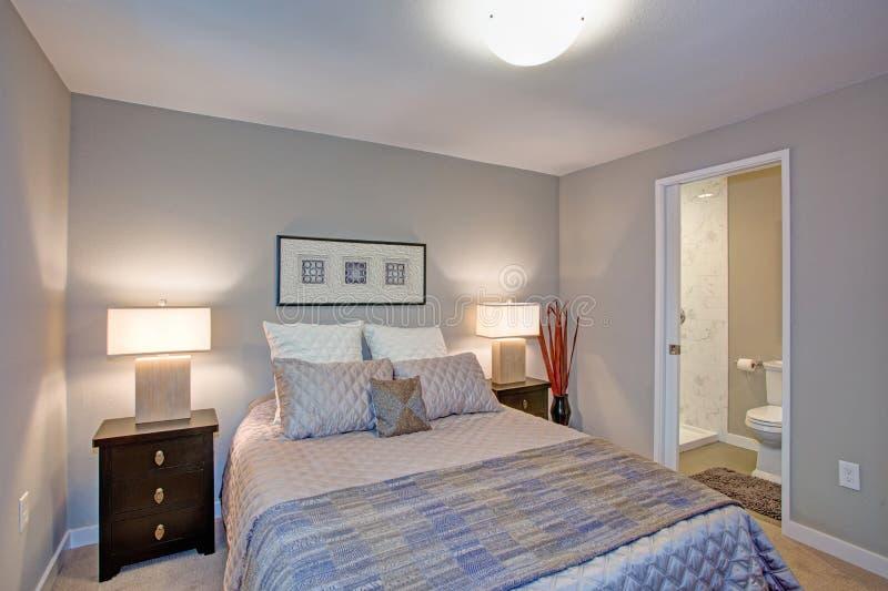 Ruhiger grauer blauer Schlafzimmerinnenraum mit ensuite Badezimmer lizenzfreie stockfotos