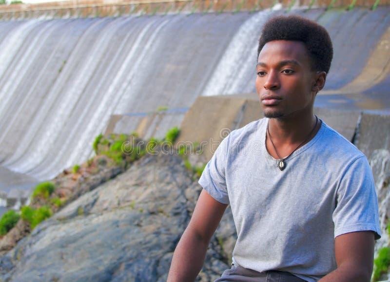Ruhiger junger Mann, der nahe dem Flussdamm sitzt lizenzfreies stockbild