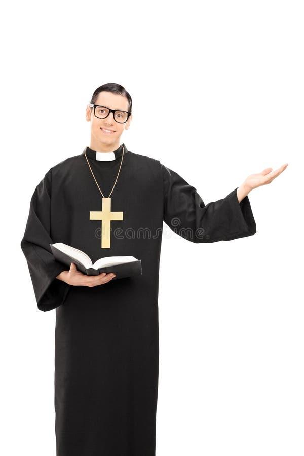 Ruhiger junger Priester, der eine Bibel hält stockbild