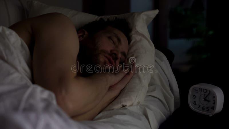 Ruhiger Mann, der auf Sofa, Uhr steht auf Nachttabelle, Spät- Rest schläft lizenzfreie stockbilder