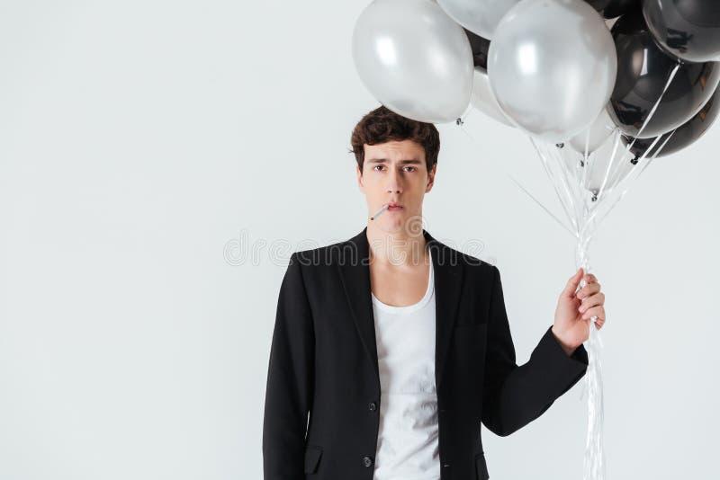 Ruhiger Mann, der Luftballone hält und Zigarette raucht stockbild