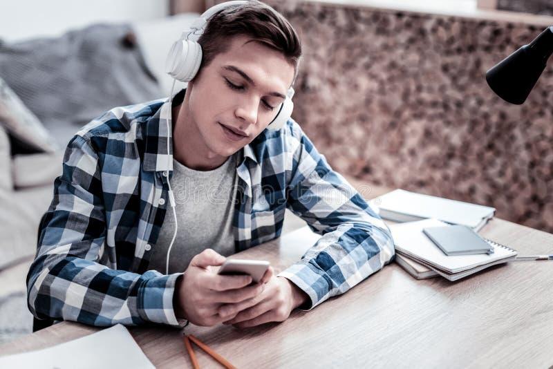 Ruhiger Mann, der seinen Smartphone beim Wählen der Musik betrachtet lizenzfreies stockfoto