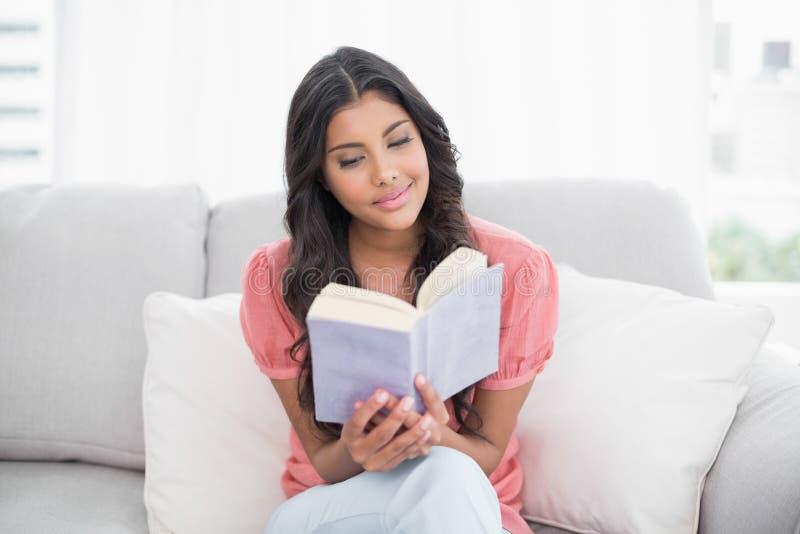 Ruhiger netter Brunette, der auf der Couch liest ein Buch sitzt stockfotografie