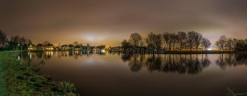 Ruhiger Panoramablick vom Fluss und von Bäumen, die durch Amsterdam-Stadt hintergrundbeleuchtet sind, beleuchtet stockbild