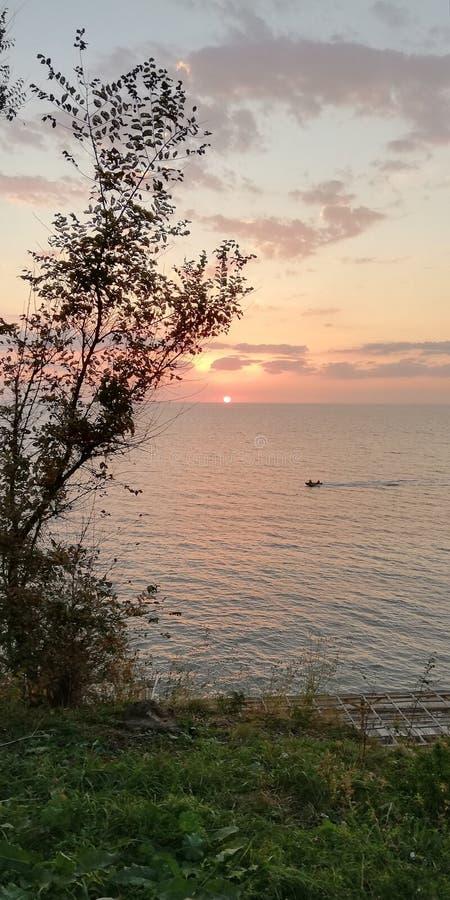 Ruhiger prächtiger natürlicher Hintergrund Boot auf der Oberfläche gegen den Hintergrund der Sonnenunterganglandschaft im Rosa un stockbild